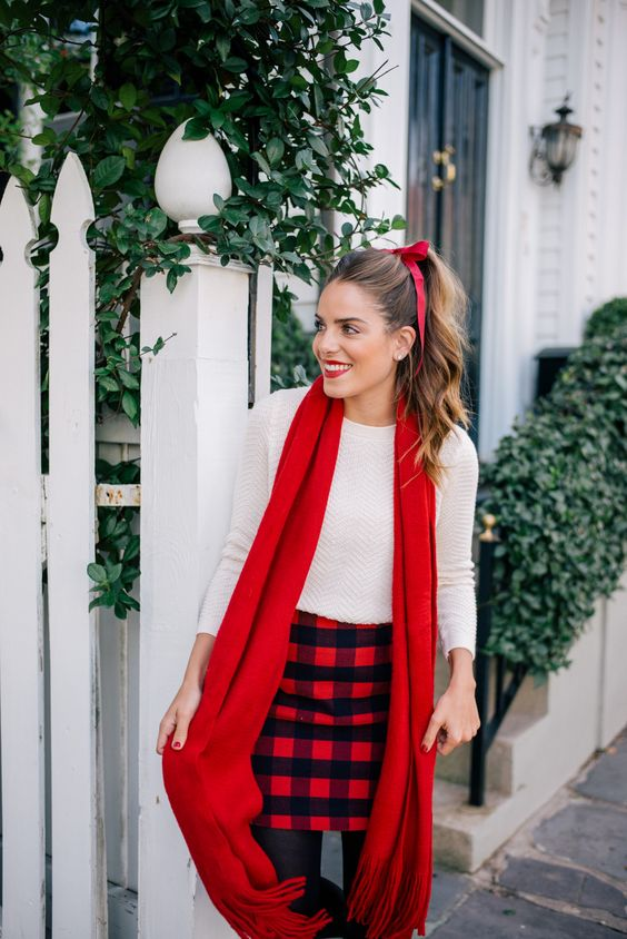 a white long sleeve top, a plaid mini, black tights and a red scarf
