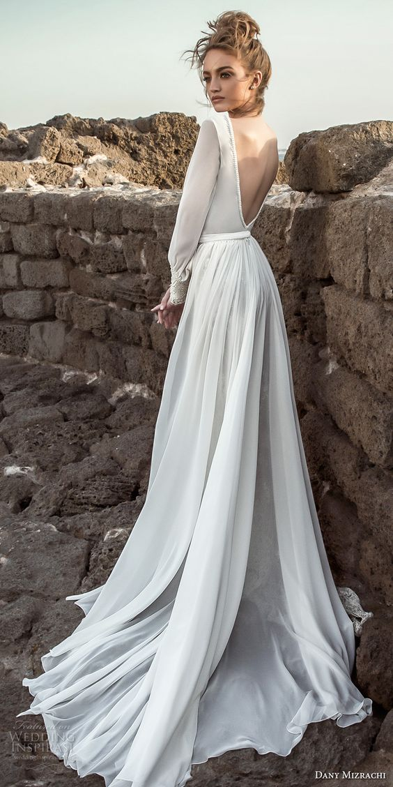 a sleek wedding dress with long sleeves, an open back and a train for a modern bride