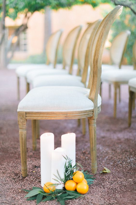 line up your wedding aisle with pillar candles, foliage and citrus to make it look chic