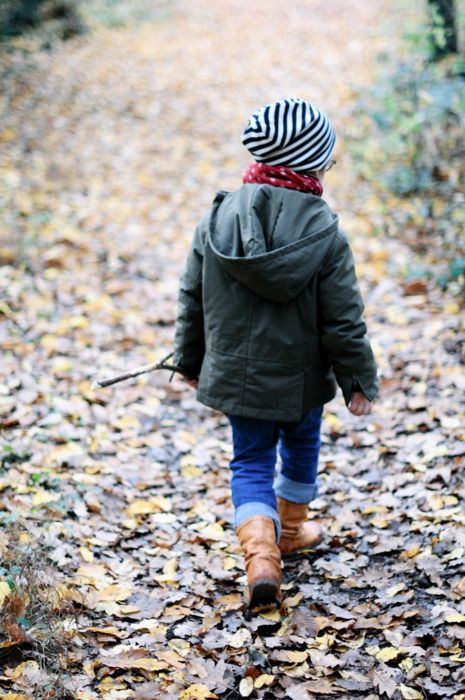 a graphite grey parka for a boy, a striped beanie and jeans, brown boots