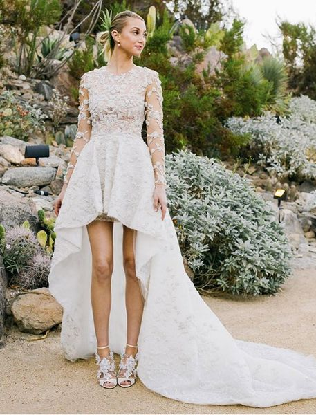 a lace applique high low wedding dress with a train, illusion sleeves and a modest neckline