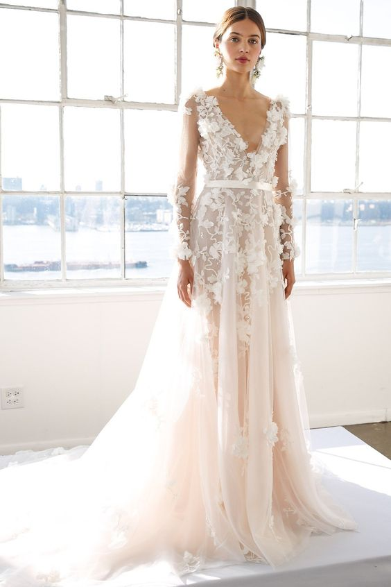 a blush wedding dress with a plunging neckline, illusion sleeves and white lace floral appliques