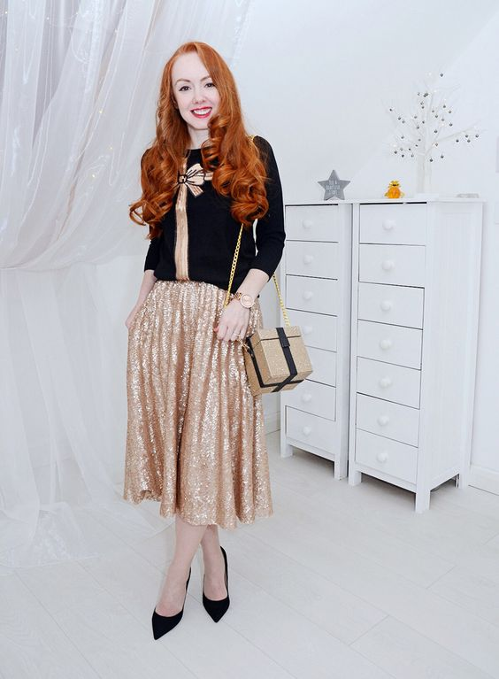 a printed black sweater with a gold bow, a gold sequin midi skirt and black pumps