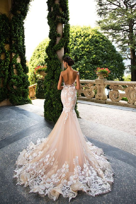 a breathtaking blush mermaid wedding dress with white lace appliques and an open back