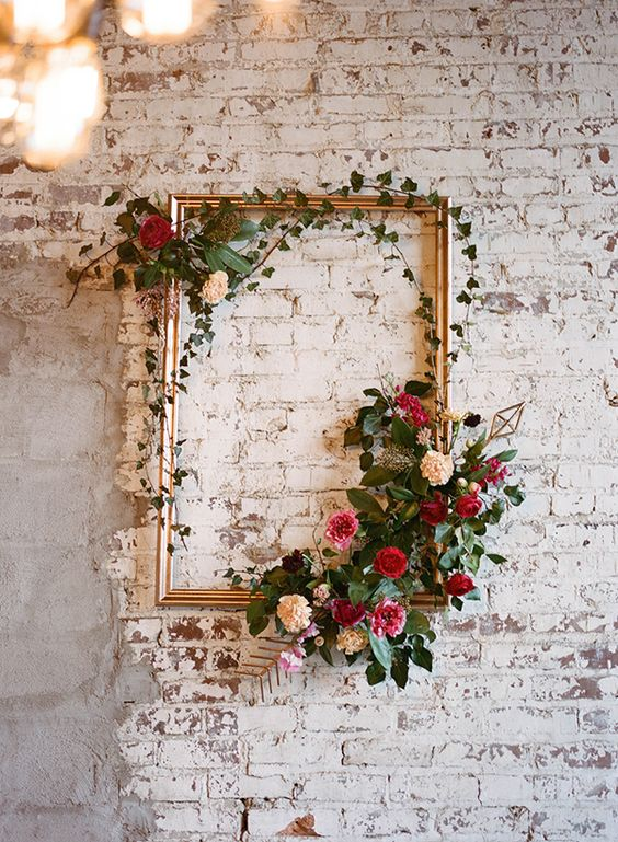a vintage picture frame decorated with greenery and blooms will be a nice artwork for your venue