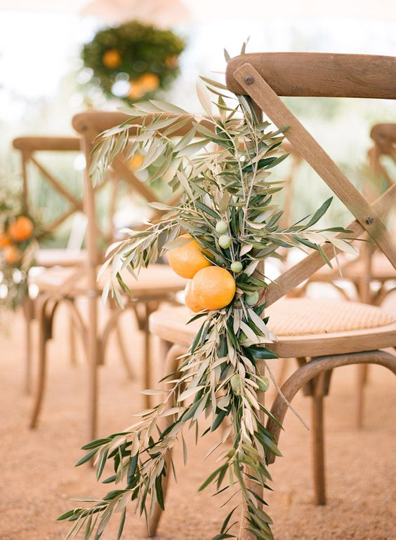 decorate chairs in the ceremony space with olive branches and oranges for a gorgeous look