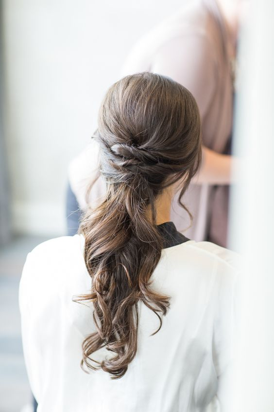 a low ponytail with twists and waves for a modern bride