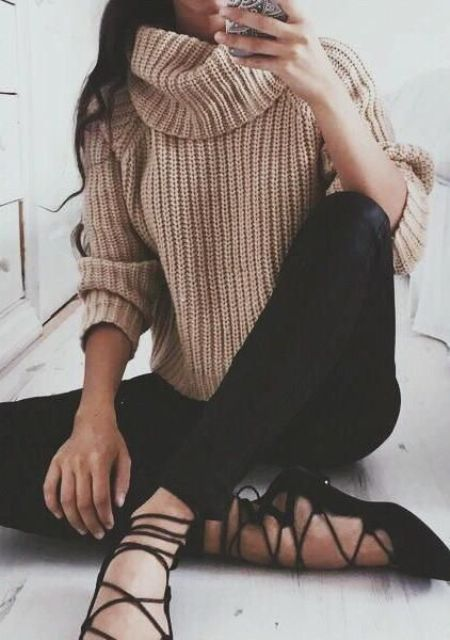 a beige chunky knit sweater, black jeans and black lace up shoes