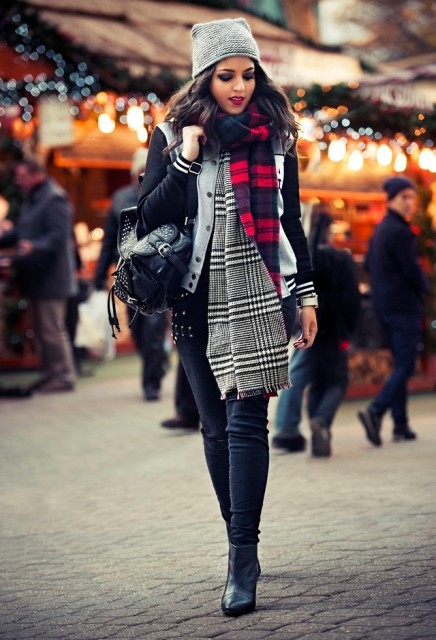 With varsity jacket, jeans, ankle boots, gray hat and black backpack