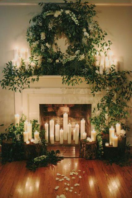 a fireplace covered with lush greenery,, lots of candles and tree stumps