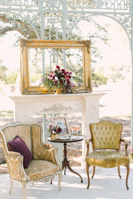an exquisite outdoor lounge with refined chairs, a faux fireplace and a vintage frame