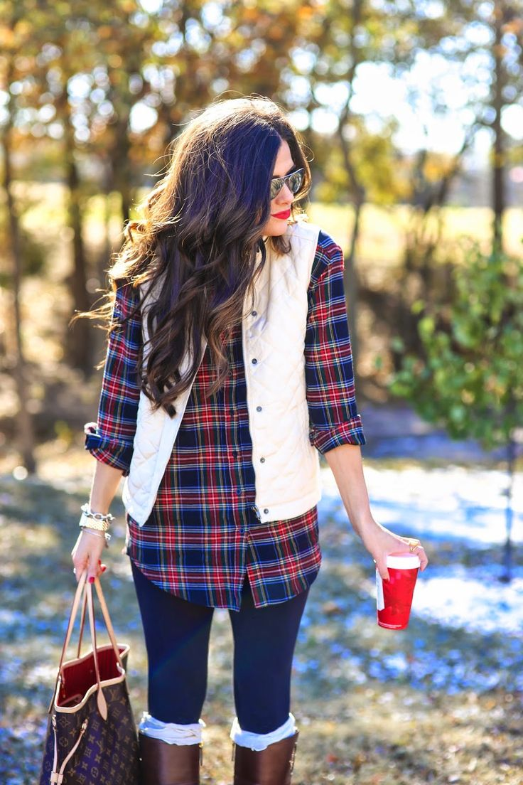 black leggings, a plaid shirt, a white quilted vest and knee boots