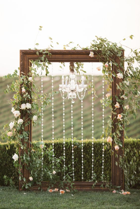 a gorgeous backdrop with a large vintage wooden frame decorated with crystals and a crystal chandelier, greenery and blush blooms