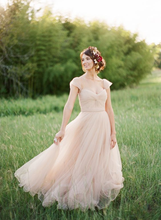 a simple romantic wedding gown with cap sleeves, a sweetheart neckline and a layered skirt