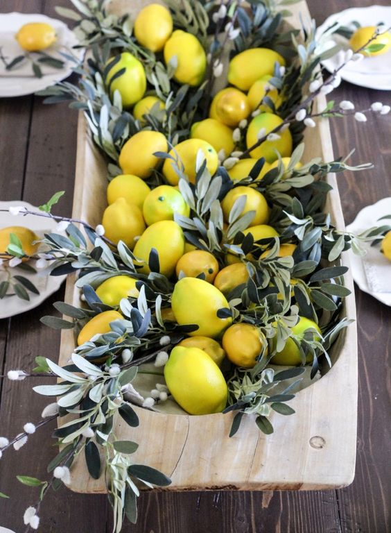 a wooden dough bowl with pussy willow and lemons for a Tuscany-inspired wedding