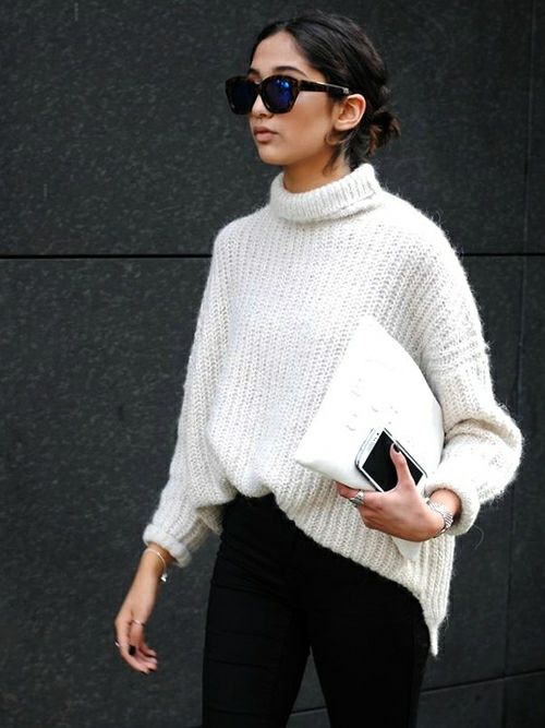 a white chunky knit sweater, black jeans and a white clutch