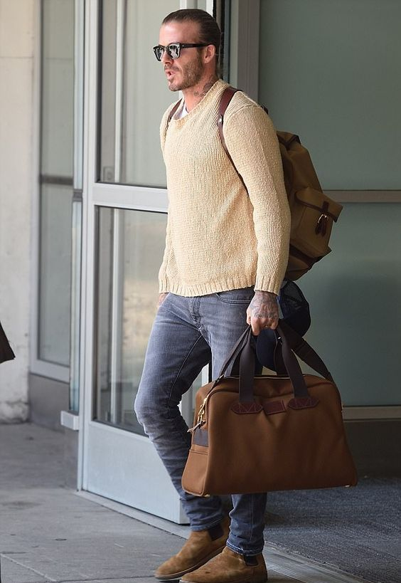 a neutral sweater over a tee, grey jeans, amber boots and a backpack