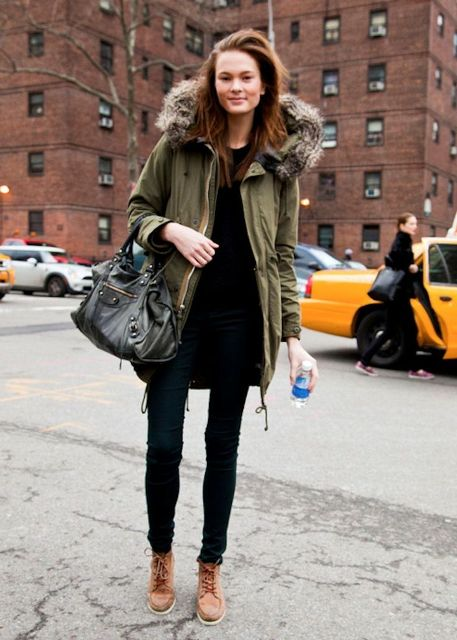 With black sweatshirt, black skinny pants, leather bag and brown boots