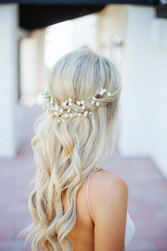 a half up with a twist and baby's breath in it, some waves for a romantic look