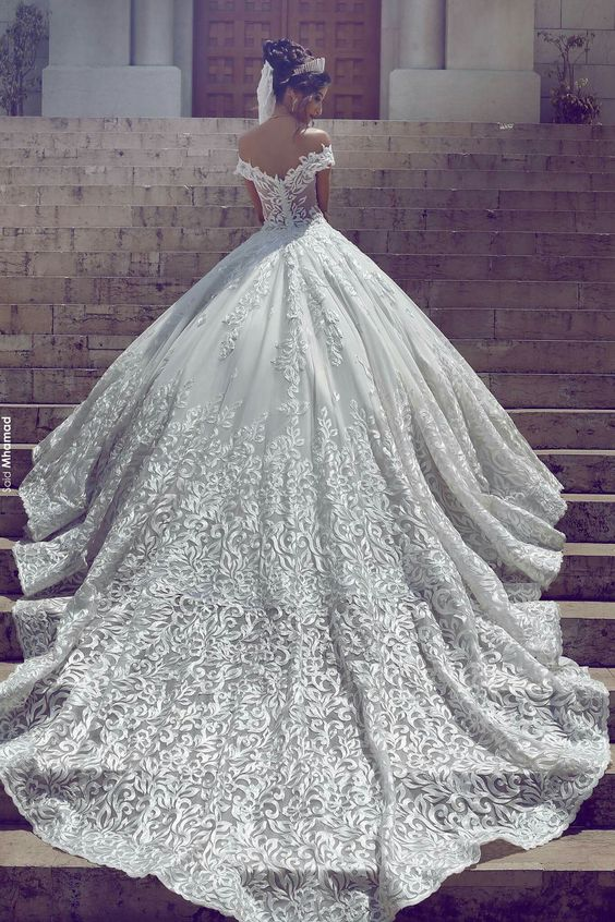 a stunning off the shoulder lace ballgown with an open back and a large and long train