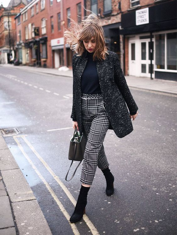 a black turtleneck, a long tweed jacket, plaid cropped pants and black sock boots