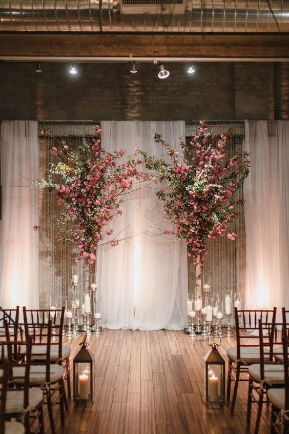 a draped fabric backdrop, lots of candles in candle holders and lush pink blooms in vases