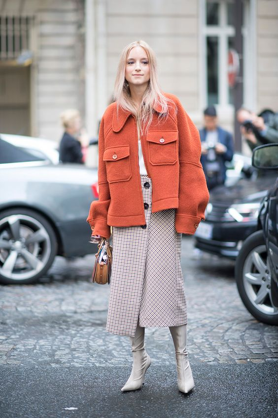 a checked wrap midi skirt with buttons, a white top, an orange short coat and creamy boots