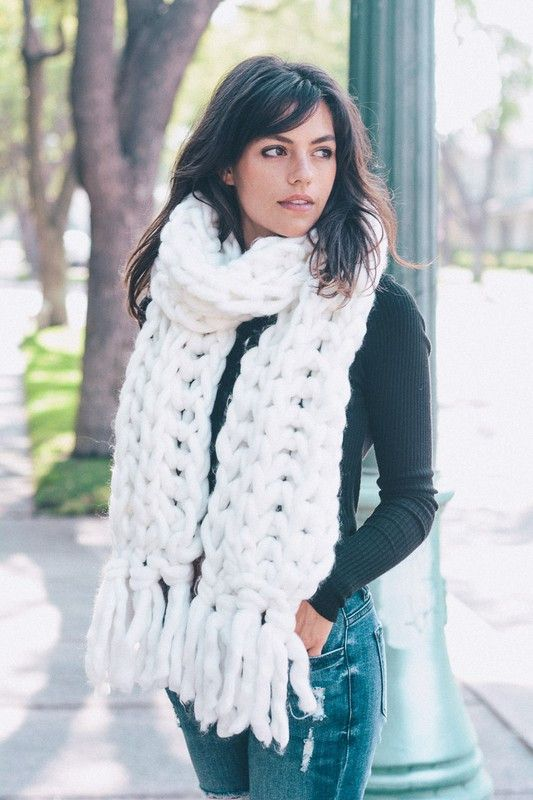 a white chunky knit scarf over a black sweater and blue jeans