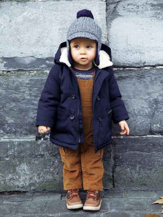 a navy boy's parka with white fur and a blue beanie