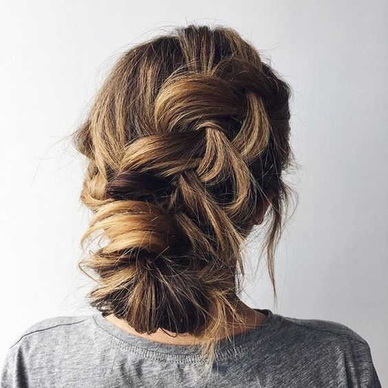 a casual messy braided low updo with bangs is ideal for those brides who don't want much mess
