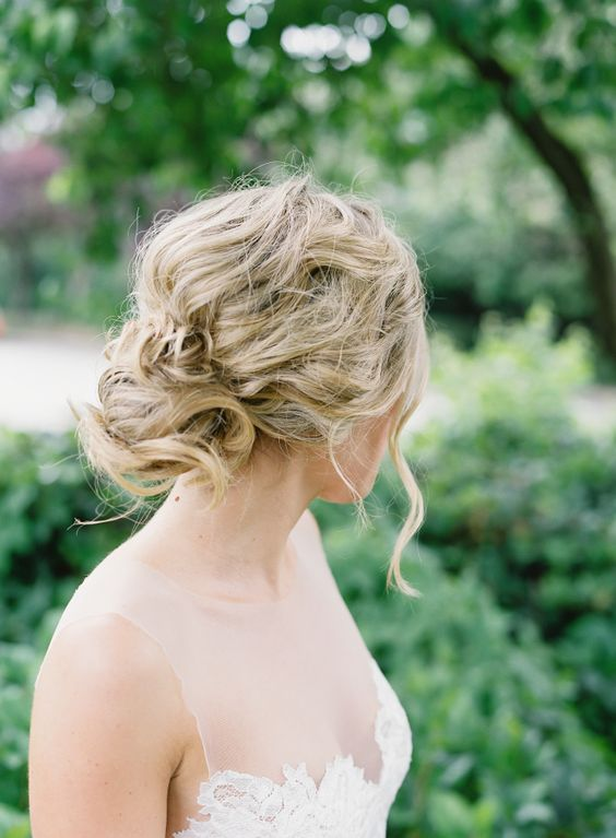 a messy wavy and twisted updo for an effortlessly chic bride