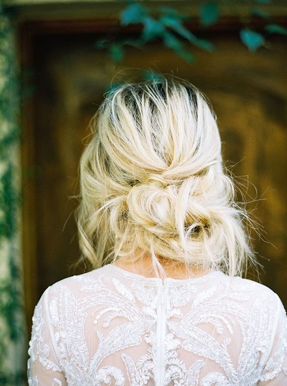 a very messy low updo with twists and bangs for an effortlessly chic look