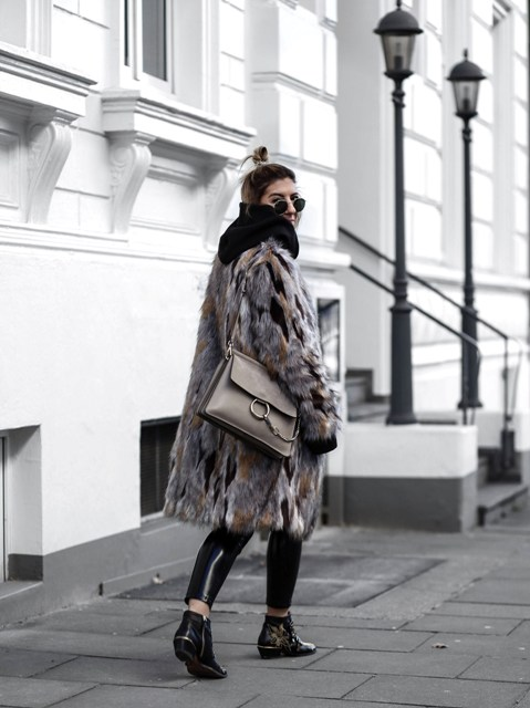 With fur coat, flat boots and gray bag