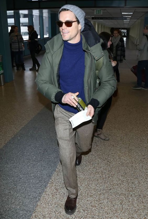 a navy sweater, neutral pants, a green puffer jacket, shoes and a beanie