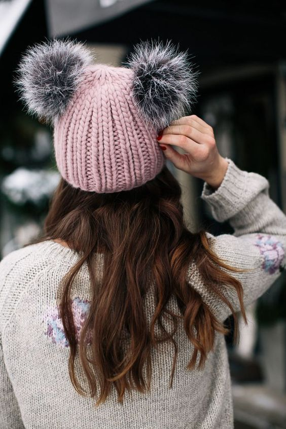 a chunky knit pink beanie with grey pompoms that imitate horns or ears