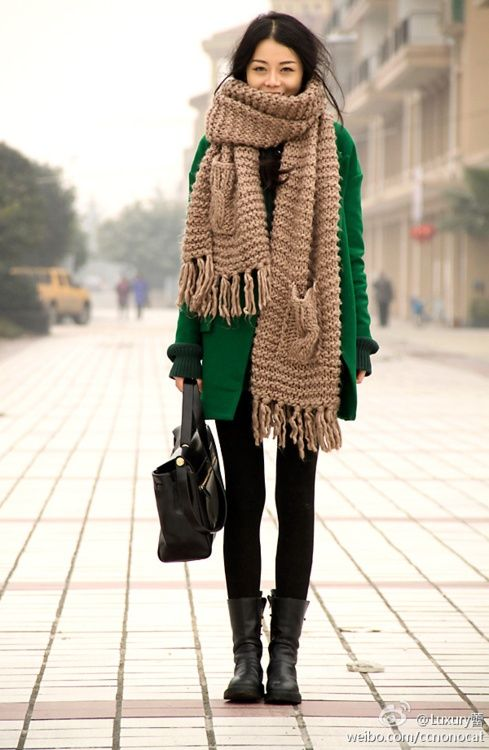an emerald coat, a beige scarf with two pockets over it and black boots