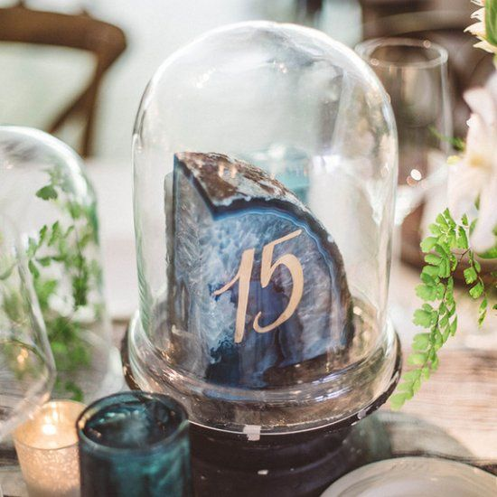 a large agate slice with a table number in a cloche is a great idea for a modern trendy wedding