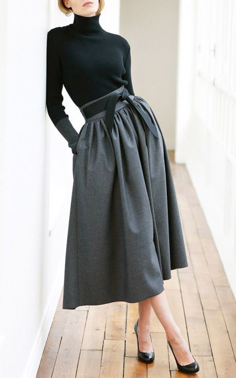 a black turtleneck, black shoes and a grey A-line full skirt with pockets
