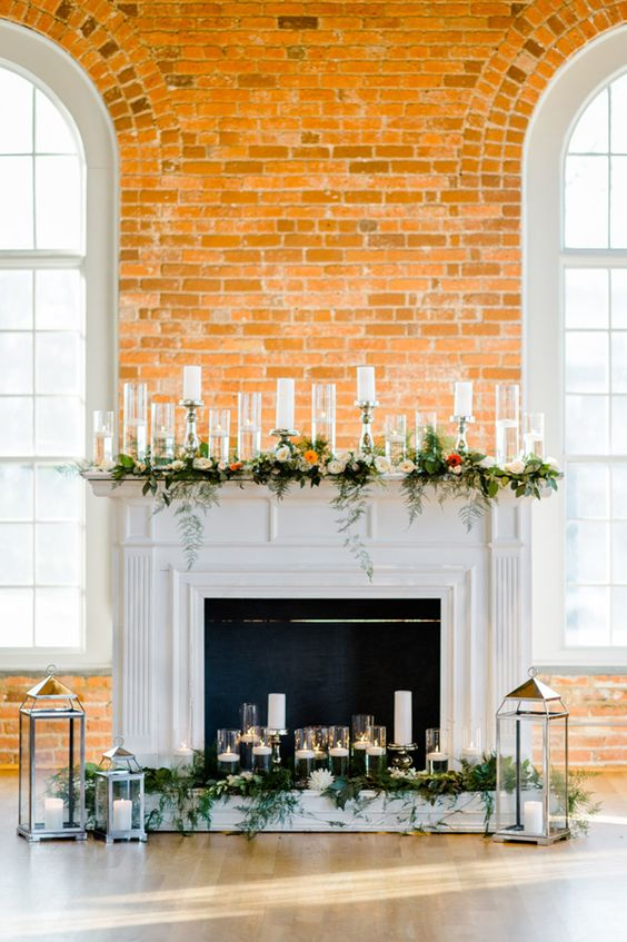 a faux fireplace decorated with greenery and bold blooms, lots of candles in candle holders and lanterns