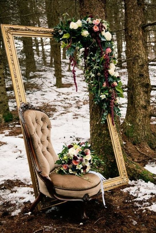 a unique outdoor photo space with a refined vintage frame and chair and lush moody florals