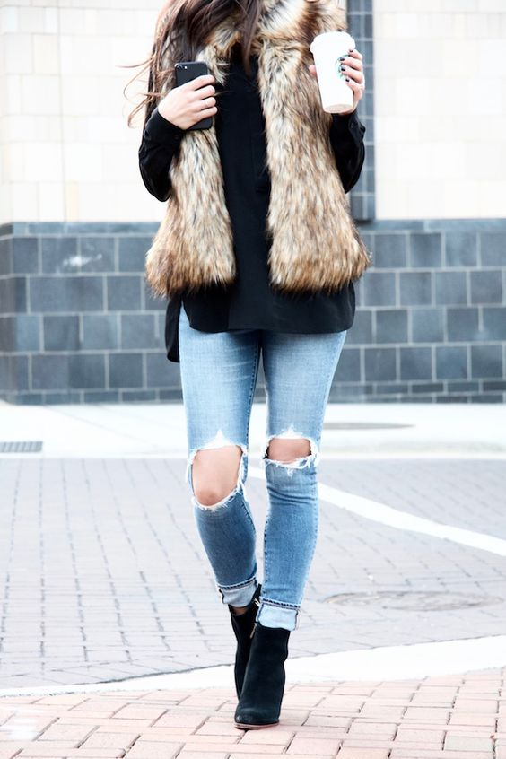 ripped jeans, a black sweater, black boots and a faux fur vest