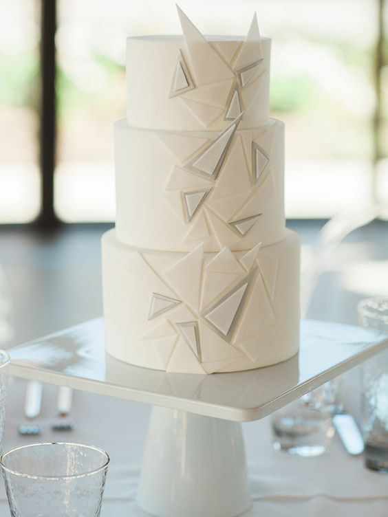 a white wedding cake with textural triangles is ideal for a minimalist wedding