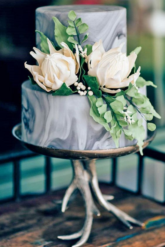 a grey marble wedding cake with edible leaves and blooms looks very interesting