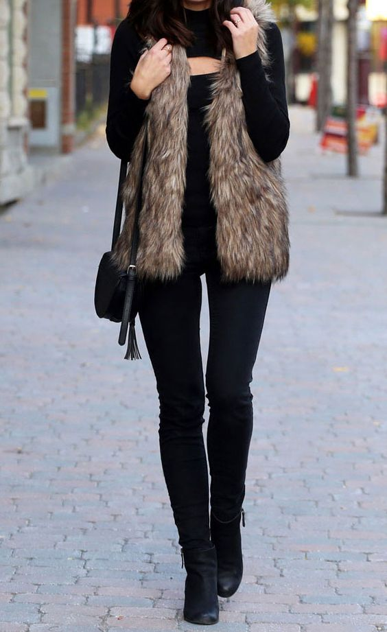 a total black look with jeans, boots, a cutout neckline sweater and a faux fur vest