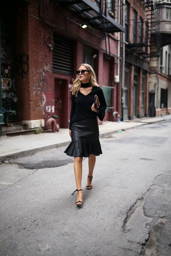 a black cutout cashmere sweater, a black leather skirt and heels