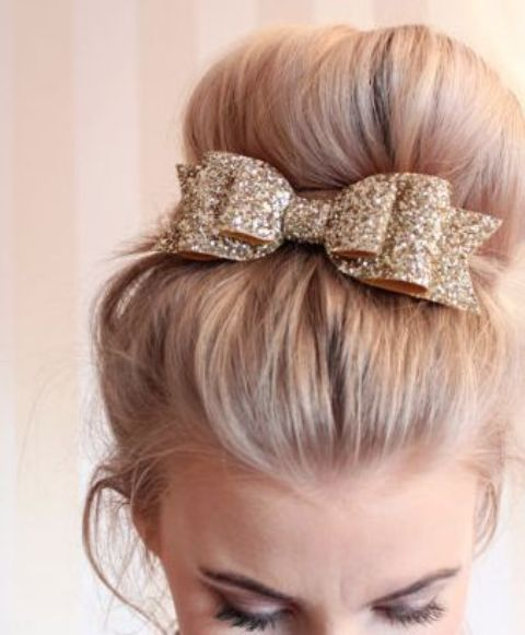 a top knot with a glitter bow looks very glam-like and cute