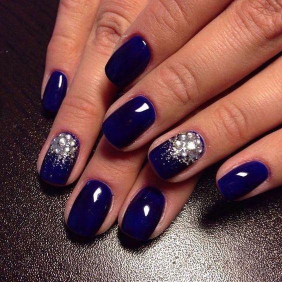 electric blue nails with large rhinestones for an accent