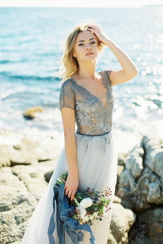 a coastal bride wearing a blue wedding gown with an illusion sequined bodice and a flowy skirt, with short sleeves and a deep V-neck