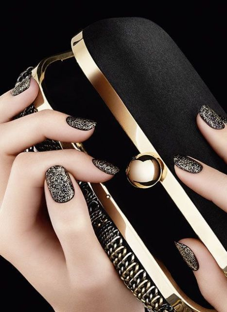 black manicure with gold glitter touches all over for a refined look