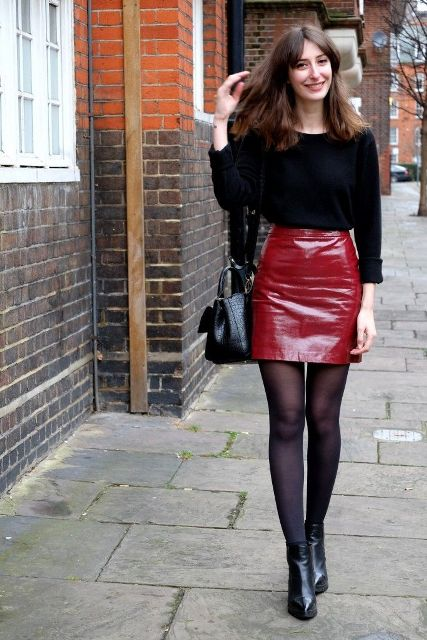 With black shirt, black tights, ankle boots and leather bag
